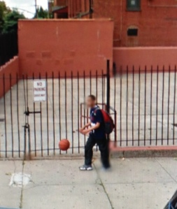 Boy dribbling outside schoolyard