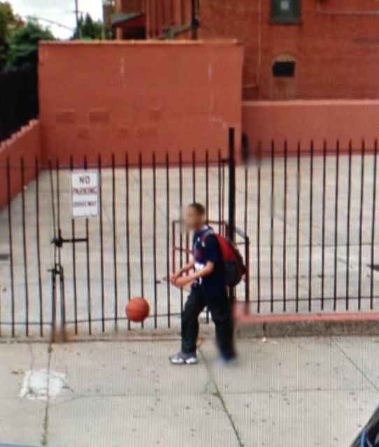 Boy dribbling outside schoolyard